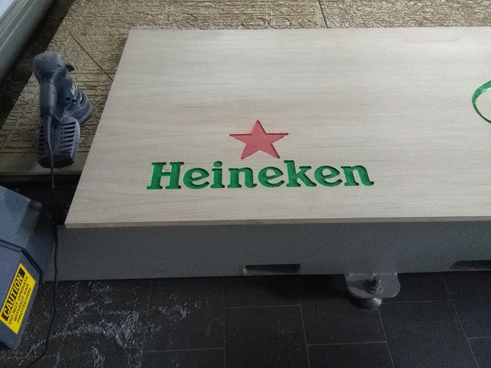 Insegna incisa su legno e colorata raffigurante il brand Heineken.